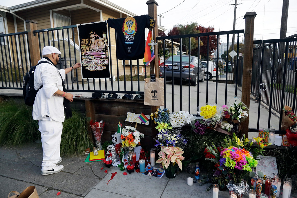 . A man places additions to a makeshift memorial for victims of a warehouse fire near the site, Monday, Dec. 5, 2016, in Oakland, Calif. The death toll in the Oakland warehouse fire climbed Monday with more bodies still feared buried in the blackened ruins, and families anxiously awaited word of their missing loved ones. (AP Photo/Marcio Jose Sanchez)