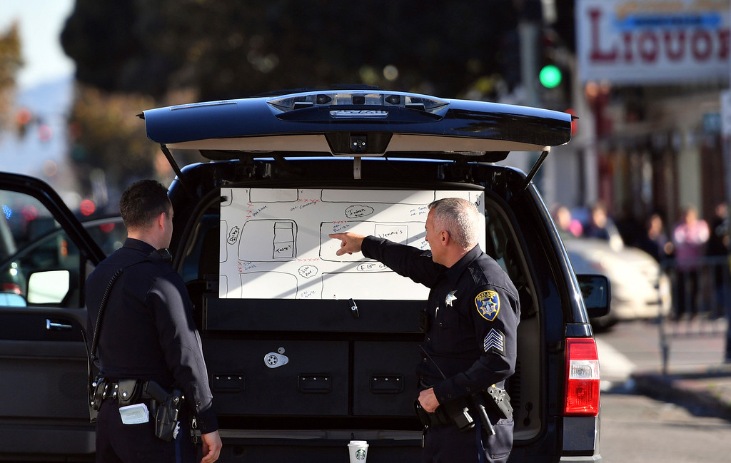 . Police officers review a map of the scene of a warehouse rave party in Oakland, Calif., where a fire killed occupants earlier in the morning on Saturday, Dec. 3, 2016. (AP Photo/Josh Edelson)
