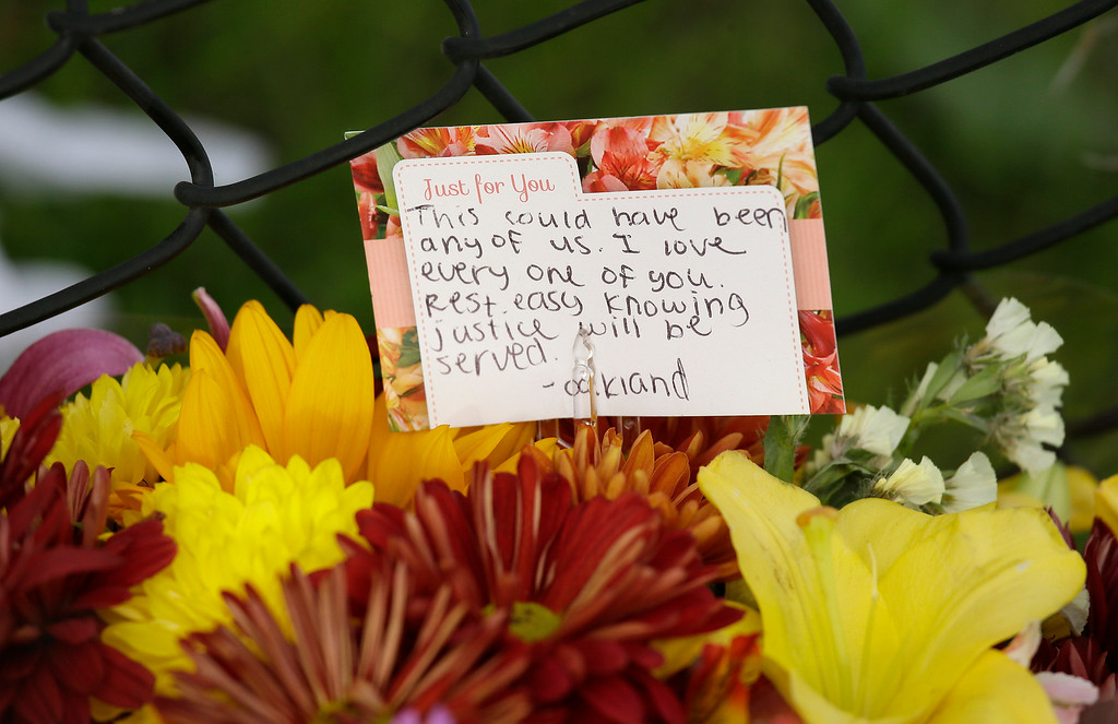 . A card and flowers are displayed at a makeshift memorial near the site of a warehouse fire Wednesday, Dec. 7, 2016, in Oakland, Calif. Recovery efforts at the site have ended officials said Wednesday.   (AP Photo/Eric Risberg)