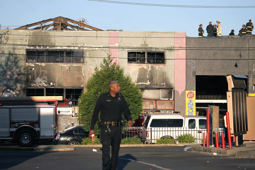 . Firefighters and police at the scene of a overnight fire that claimed the lives of at least nine people at a warehouse in the Fruitvale neighborhood on December 3, 2016 in Oakland, California. The warehouse was hosting an electronic music party.  (Photo by Elijah Nouvelage/Getty Images)