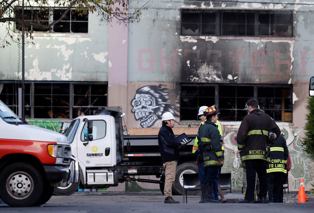 . Emergency crews work in front of the site of a warehouse fire, Monday, Dec. 5, 2016, in Oakland, Calif. The death toll in the Oakland warehouse fire climbed Monday with more bodies still feared buried in the blackened ruins, and families anxiously awaited word of their missing loved ones. (AP Photo/Marcio Jose Sanchez)