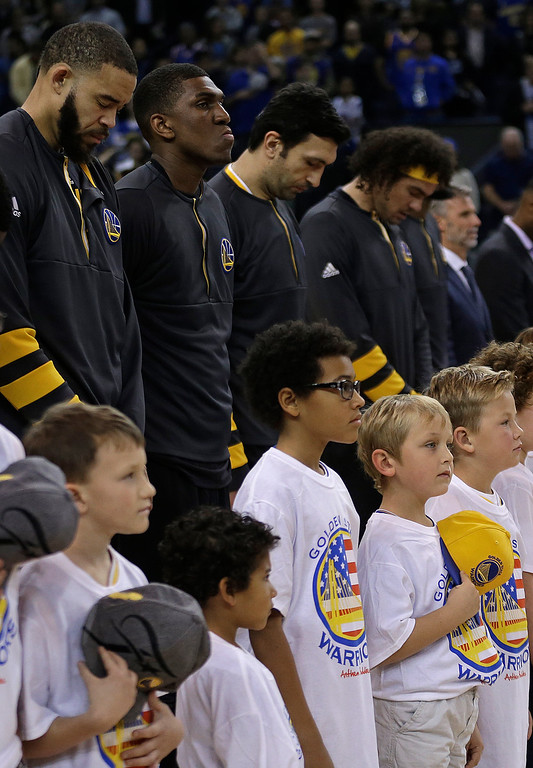. Golden State Warriors, back row, and children observe a moment of silence for victims of a warehouse fire in Oakland, Calif., prior to an NBA basketball game against the Phoenix Suns on Saturday, Dec. 3, 2016. (AP Photo/Ben Margot)