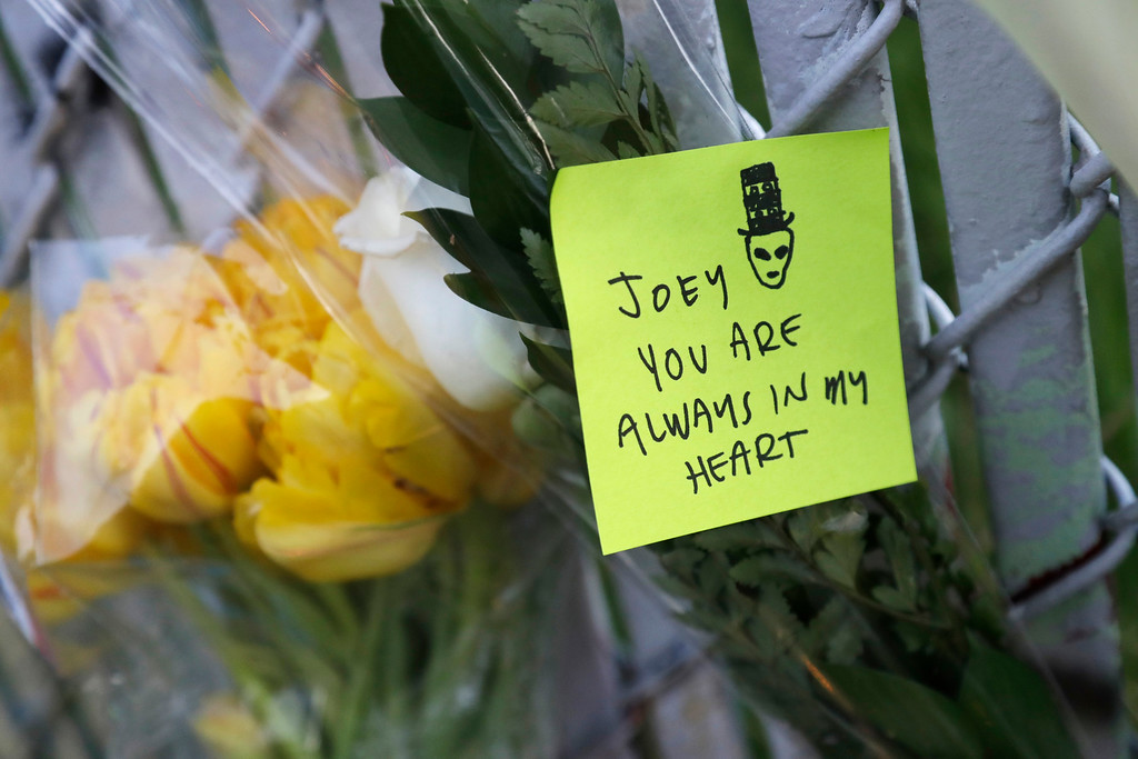 . A note with flowers hangs on a fence near the site of a warehouse fire Monday, Dec. 5, 2016, in Oakland, Calif. The death toll in the Oakland warehouse on Friday fire climbed Monday with more bodies still feared buried in the blackened ruins, and families anxiously awaited word of their missing loved ones. (AP Photo/Marcio Jose Sanchez)