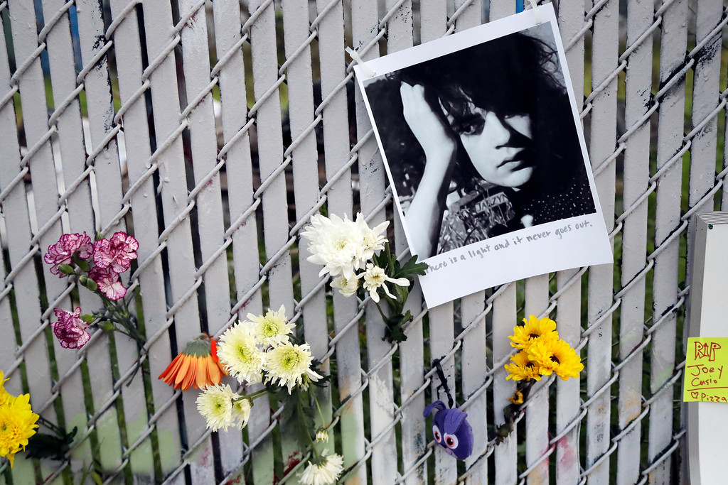 . Pictures and flowers adorn a fence near the site of a warehouse fire Monday, Dec. 5, 2016, in Oakland, Calif. The death toll in the Oakland warehouse fire climbed Monday with more bodies still feared buried in the blackened ruins, and families anxiously awaited word of their missing loved ones. (AP Photo/Marcio Jose Sanchez)