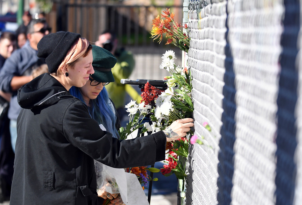 . People place flowers near the scene of a warehouse fire Saturday, Dec. 3, 2016, in Oakland, Calif. A deadly fire broke out during a rave at the converted warehouse in the San Francisco Bay Area. (AP Photo/Josh Edelson)