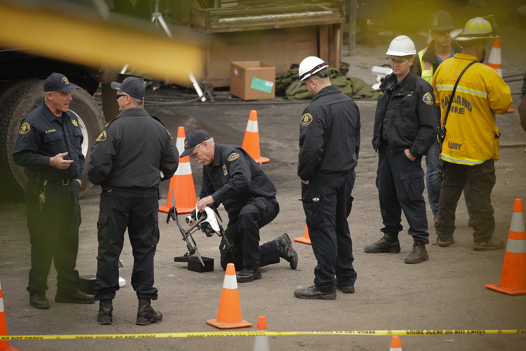 . OAKLAND, CA - DECEMBER 05: Law enforcement officers work with a drone equipped with a thermal imaging camera at the site of a warehouse fire that has claimed the lives of at least thirty-six people on December 5, 2016 in Oakland, California. The fire took place during a musical event late Friday night. (Photo by Elijah Nouvelage/Getty Images)