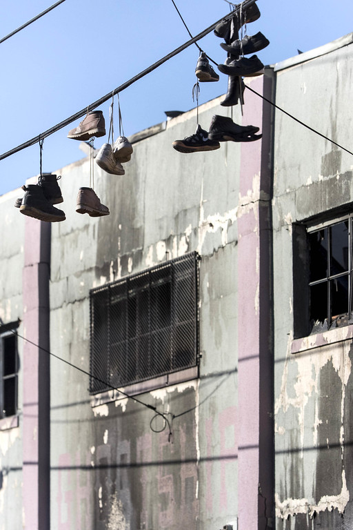 . December 3, 2016 - Oakland, California, U.S.- Shoes hang from a line at the scene of a warehouse fire that killed at least nine people at 31st Ave. and International Blvd. at 11:30 p.m. on Friday night, Dec. 2, 2016. Officials fear dozens may have died in the fire that swept through an Oakland warehouse where a concert was. (Credit Image: © Paul Kuroda via ZUMA Wire)