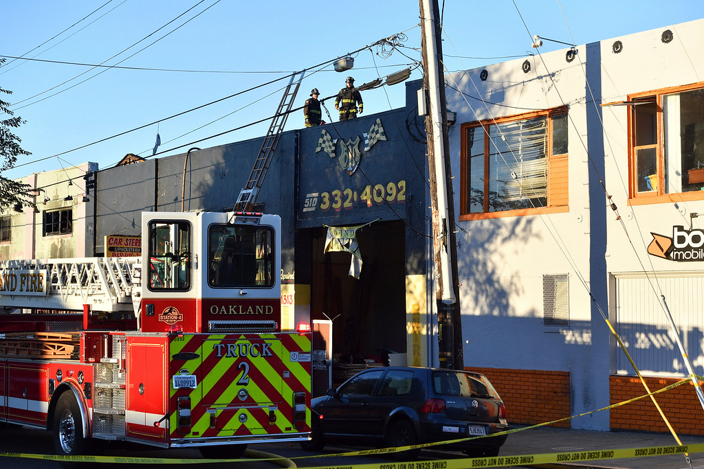 . Firefighters assess the scene where a fire tore through a warehouse party early Saturday, Dec. 3, 2016 in Oakland.   The blaze began at about 11:30 p.m. on Friday during a party at a warehouse in the San Francisco Bay Area city.  Several people are unaccounted for.  (AP Photo/Josh Edelson)
