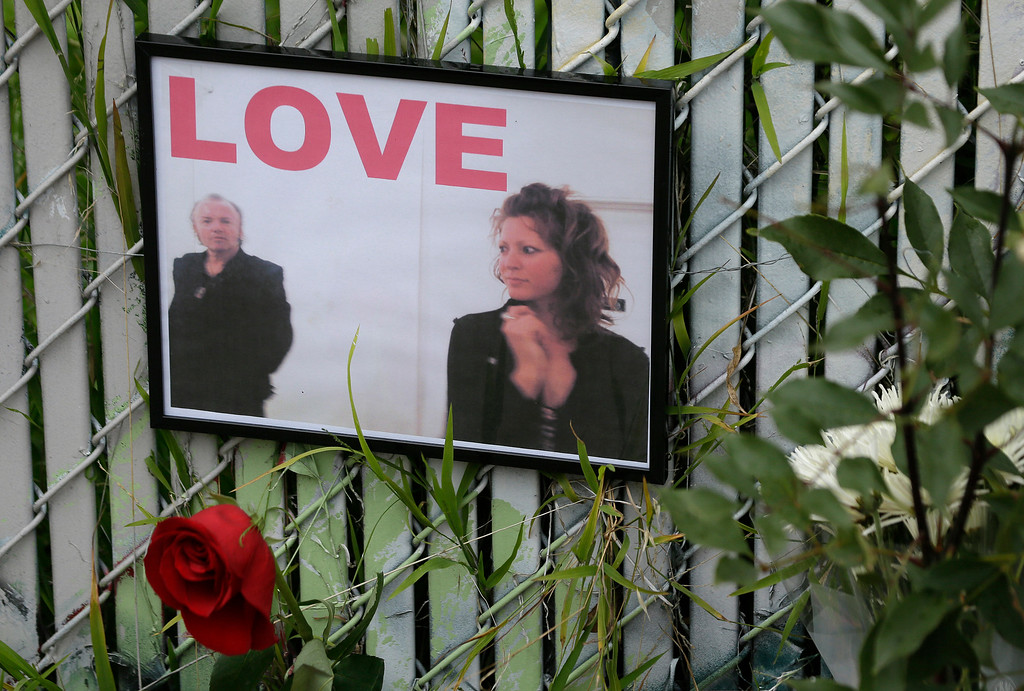 . A pair of photographs hang from a fence at a makeshift memorial near the site of a warehouse fire Wednesday, Dec. 7, 2016, in Oakland, Calif. The fire that killed 36 people during a dance party at an Oakland warehouse grew rapidly and was raging by the time people on the second floor of the building detected it, trapping them upstairs, investigators said. (AP Photo/Eric Risberg)