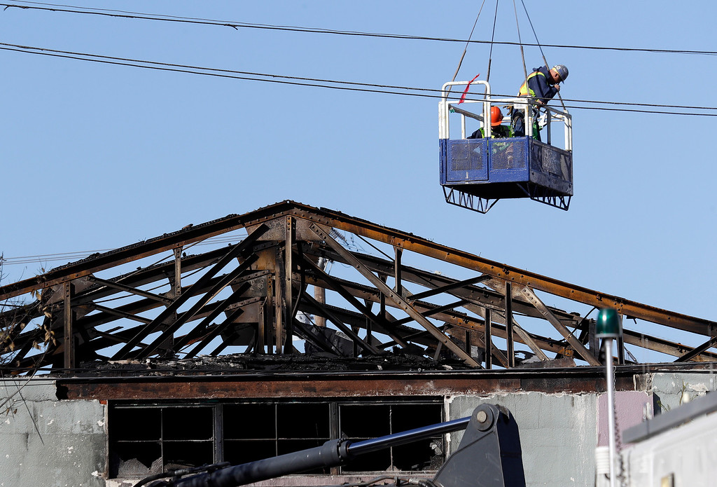 . A search and rescue team is lowered into the site of a warehouse fire Tuesday, Dec. 6, 2016, in Oakland, Calif. (AP Photo/Marcio Jose Sanchez)