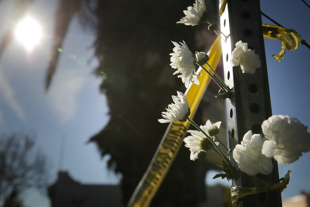 . OAKLAND, CA - DECEMBER 03: Flowers are placed on a post outside a police line following an overnight fire that claimed the lives of at least nine people at a warehouse in the Fruitvale neighborhood on December 3, 2016 in Oakland, California. The warehouse was hosting an electronic music party.  (Photo by Elijah Nouvelage/Getty Images)