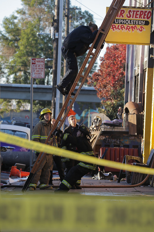 . OAKLAND, CA - DECEMBER 03:  Fire department members investigate the scene of a overnight fire that claimed the lives of at least nine people at a warehouse in the Fruitvale neighborhood on December 3, 2016 in Oakland, California. The warehouse was hosting an electronic music party.  (Photo by Elijah Nouvelage/Getty Images)
