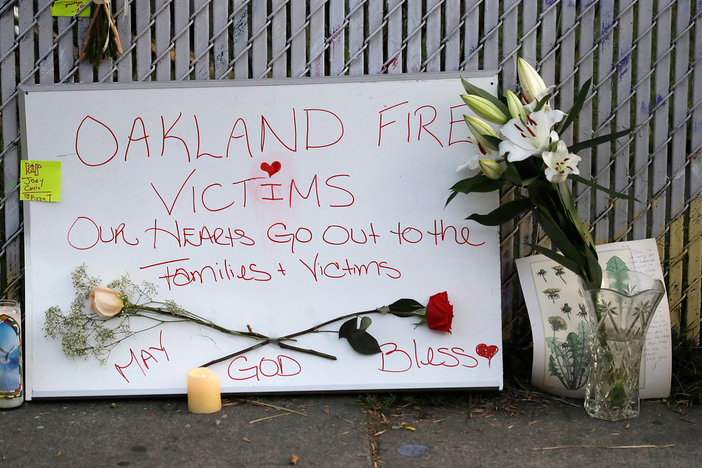 . Signs and flowers adorn a fence near the site of a warehouse fire Monday, Dec. 5, 2016, in Oakland, Calif. The death toll in the Oakland warehouse fire on Friday climbed Monday with more bodies still feared buried in the blackened ruins, and families anxiously awaited word of their missing loved ones. (AP Photo/Marcio Jose Sanchez)