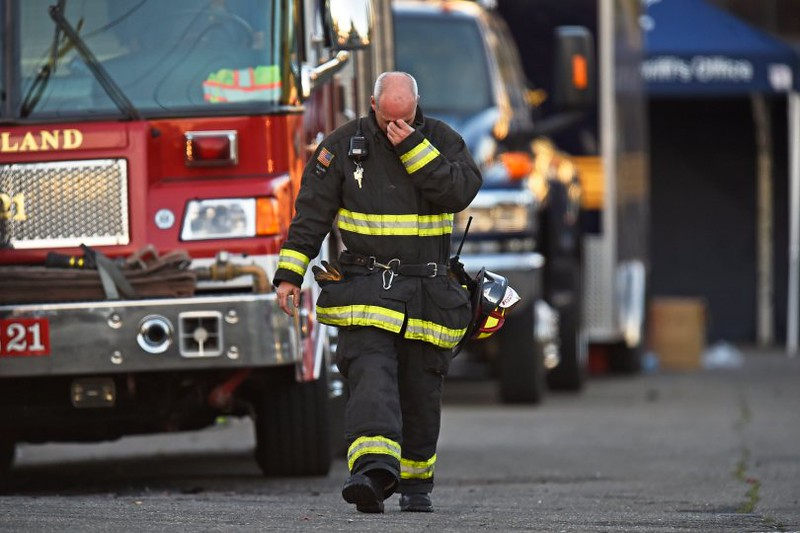 . Oakland firefighter Lt. Freelen, from Engine 13, reacts while walking away from the scene of a warehouse fire in Oakland, Calif. on Saturday, Dec. 3, 2016. The fire tore through the two-story building on the 1300 block of 31st Avenue at about 11:30 p.m. late Friday evening. The fire killed at least 9 people. (Photo by Jose Carlos Fajardo/Bay Area News Group)