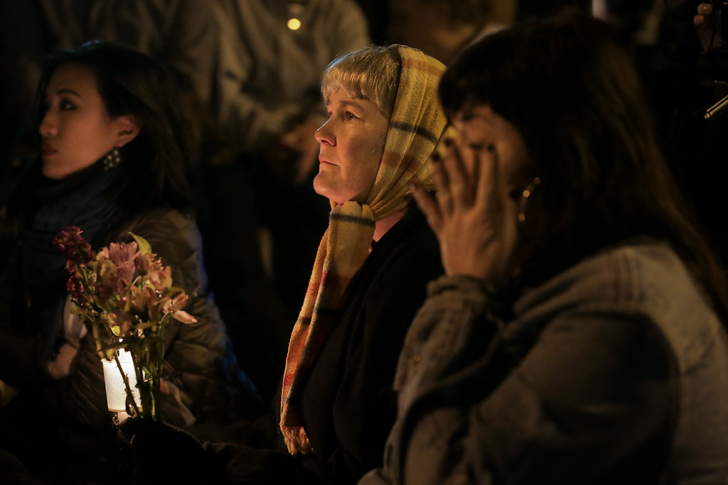 . OAKLAND, CA - DECEMBER 05: Three women attend a vigil for the victims of a warehouse fire that has claimed the lives of at least thirty-six people on December 5, 2016 in Oakland, California. The fire took place during a musical event late Friday night. (Photo by Elijah Nouvelage/Getty Images)