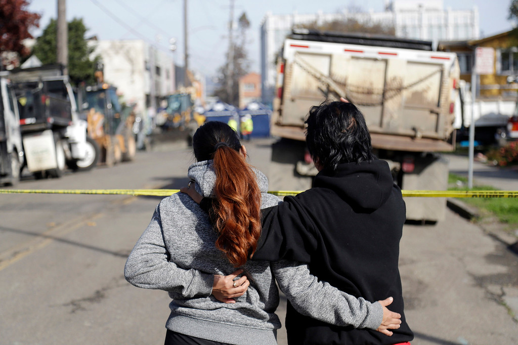 . Two women watch the scene of a warehouse fire, Sunday, Dec. 4, 2016, in Oakland, Calif. Officials said they are continuing to search the charred rubble from the fatal fire that ripped through a late-night dance party in a converted warehouse earlier in the weekend. (AP Photo/Marcio Jose Sanchez)