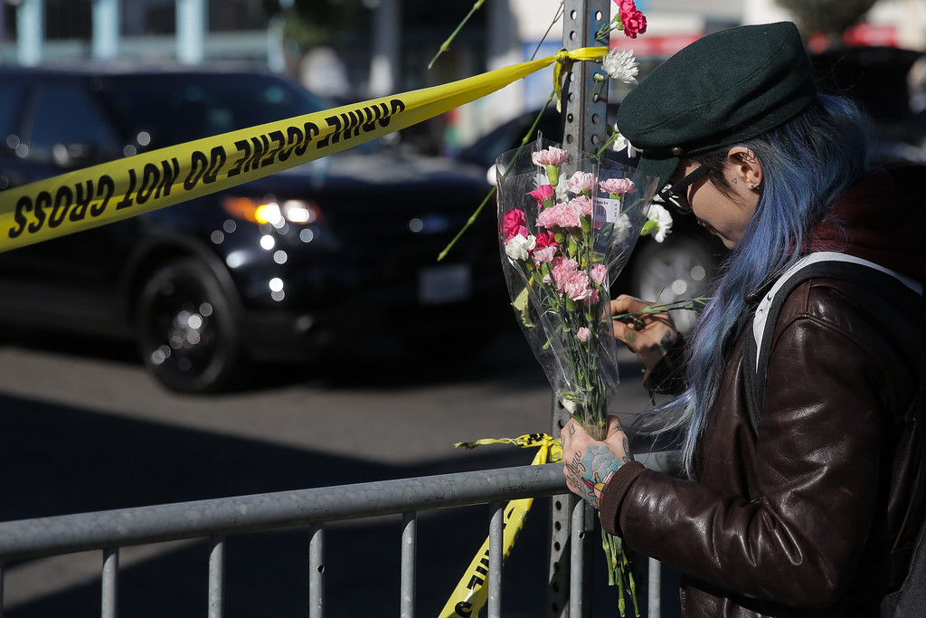 . OAKLAND, CA - DECEMBER 03: A woman places flowers on a post outside a police line  following an overnight fire that claimed the lives of at least nine people at a warehouse in the Fruitvale neighborhood on December 3, 2016 in Oakland, California. The warehouse was hosting an electronic music party.  (Photo by Elijah Nouvelage/Getty Imag
