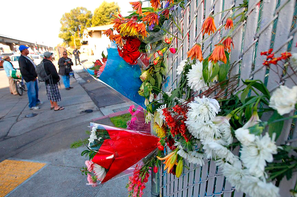 . Flowers left on a fence along E. 12th Street and the corner of 31st Avenue are photographed on Sunday, Dec. 4, 2016, in Oakland, Calif.  The Alameda County Sheriff\'s Office annouced 24 bodies have been found so far, inside a warehouse after a deadly fire occured on Friday, December 2, 2016.  (Aric Crabb/Bay Area News Group)