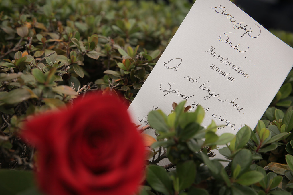 . OAKLAND, CA - DECEMBER 05: A card with a handwritten message is seen by a rose near the site a warehouse fire which has so far claimed the lives of at least thirty-six people on December 5, 2016 in Oakland, California. The fire took place during a musical event late Friday night. (Photo by Elijah Nouvelage/Getty Images)