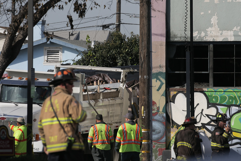 . OAKLAND, CA - DECEMBER 04: Workers clear debris following a warehouse fire that has claimed the lives of at least thirty people on December 4, 2016 in Oakland, California. The fire took place during a musical event late Friday night. (Photo by Elijah Nouvelage/Getty Images)