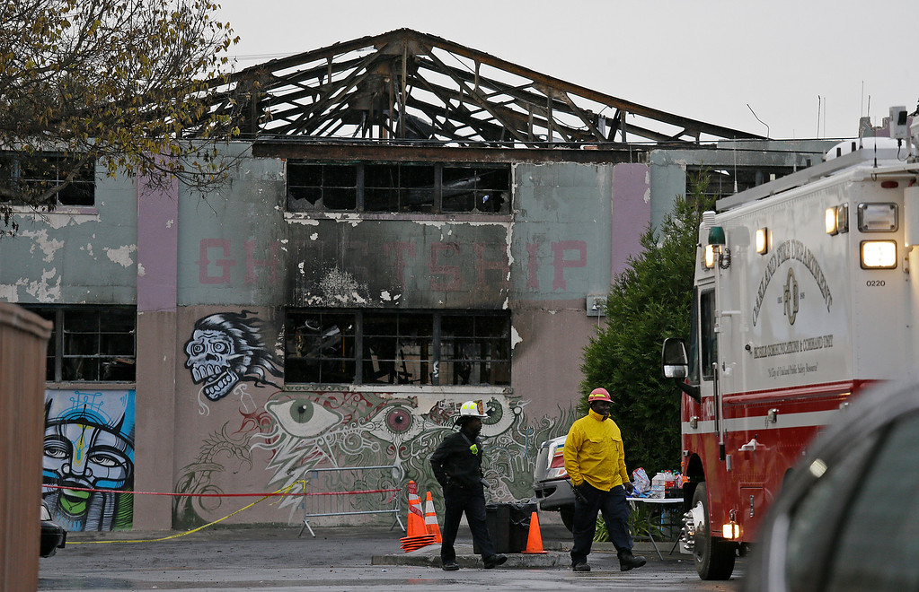 . A pair of Oakland fire officials walk past the remains of the Ghost Ship warehouse fire Wednesday, Dec. 7, 2016, in Oakland, Calif. The fire that killed 36 people during a party at an Oakland warehouse started on the ground floor and quickly raged, with smoke billowing into the second level and trapping victims whose only escape route was through the flames, federal investigators said Wednesday. (AP Photo/Eric Risberg)