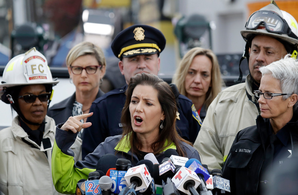 . Oakland Mayor Libby Schaaf, center, is flanked by emergency personnel during a press conference near the site of a warehouse fire Monday, Dec. 5, 2016, in Oakland, Calif. The death toll in the fire climbed Monday with more bodies still feared buried in the blackened ruins, and families anxiously awaited word of their missing loved ones. (AP Photo/Marcio Jose Sanchez)