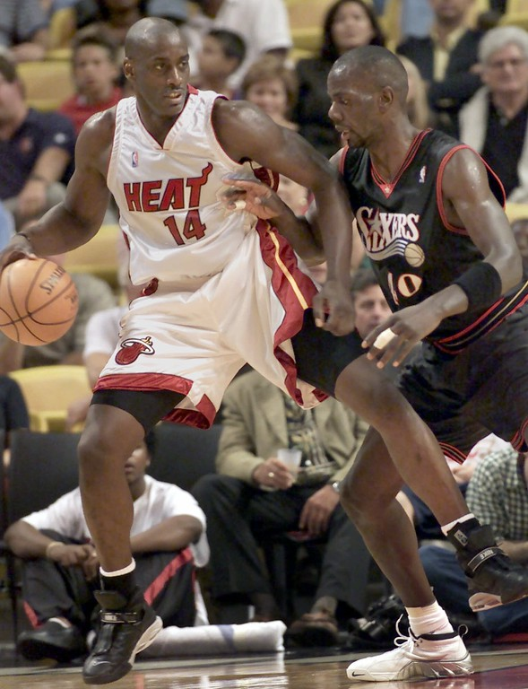 . Miami Heat forward Anthony Mason (14) attempts to drive past Philadelphia 76ers forward Tyrone Hill, right, in the first quarter Saturday, Nov. 4, 2000, in Miami. (AP Photo/Wilfredo Lee)
