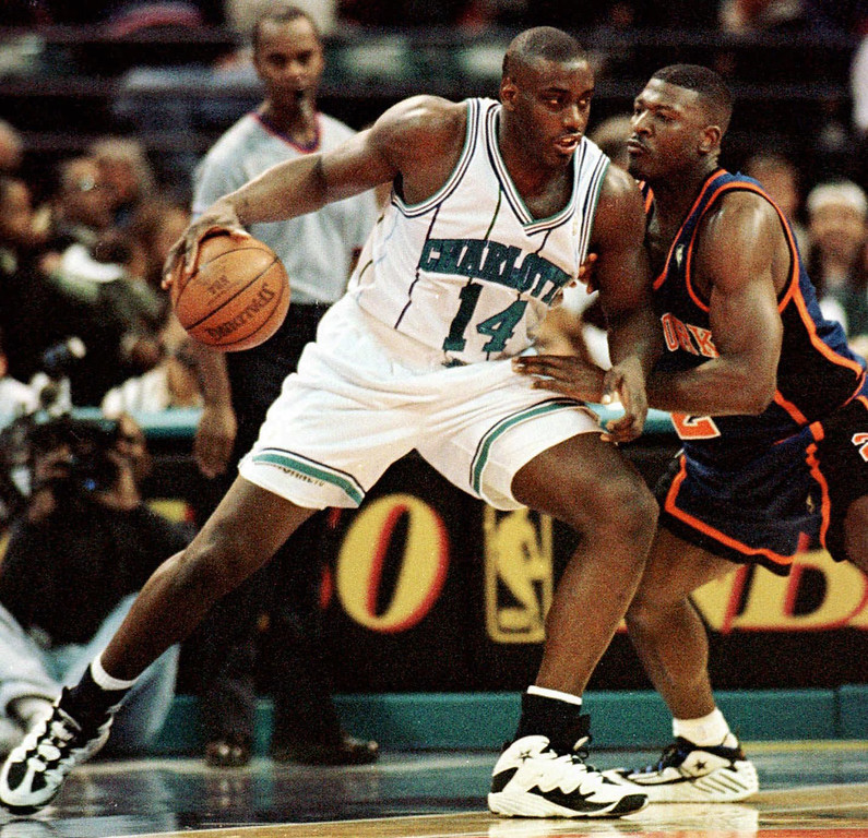 . FILE - In this Nov. 20, 1996 file photo, Charlotte Hornets forward Anthony Mason, left,  leans in on New York Knicks forward Larry Johnson during first quarter of an NBA basketball game in Charlotte, N.C.  The New York Knicks spokesman Jonathan Supranowitz confirmed Saturday, Feb. 28, 2015 that Mason, a rugged power forward who was a defensive force for several NBA teams in the 1990s, has died. He was 48. (AP Photo/Peter A. Harris)