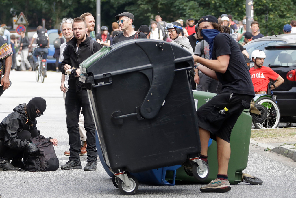 . Demonstrators turn waste bins on the first day of the G-20 summit in Hamburg, northern Germany, Friday, July 7, 2017. The leaders of the group of 20 meet July 7 and 8. (AP Photo/Matthias Schrader)