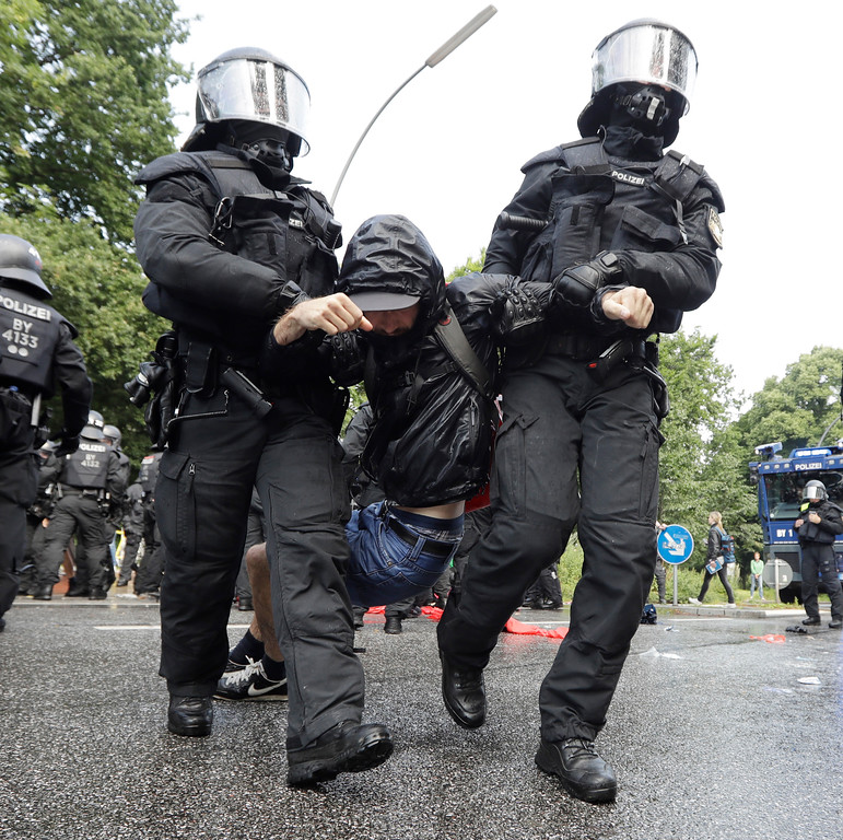 . Police officers carry a demonstrator who blocked a street on the first day of the G-20 summit in Hamburg, northern Germany, Friday, July 7, 2017. The leaders of the group of 20 meet July 7 and 8. (AP Photo/Matthias Schrader)