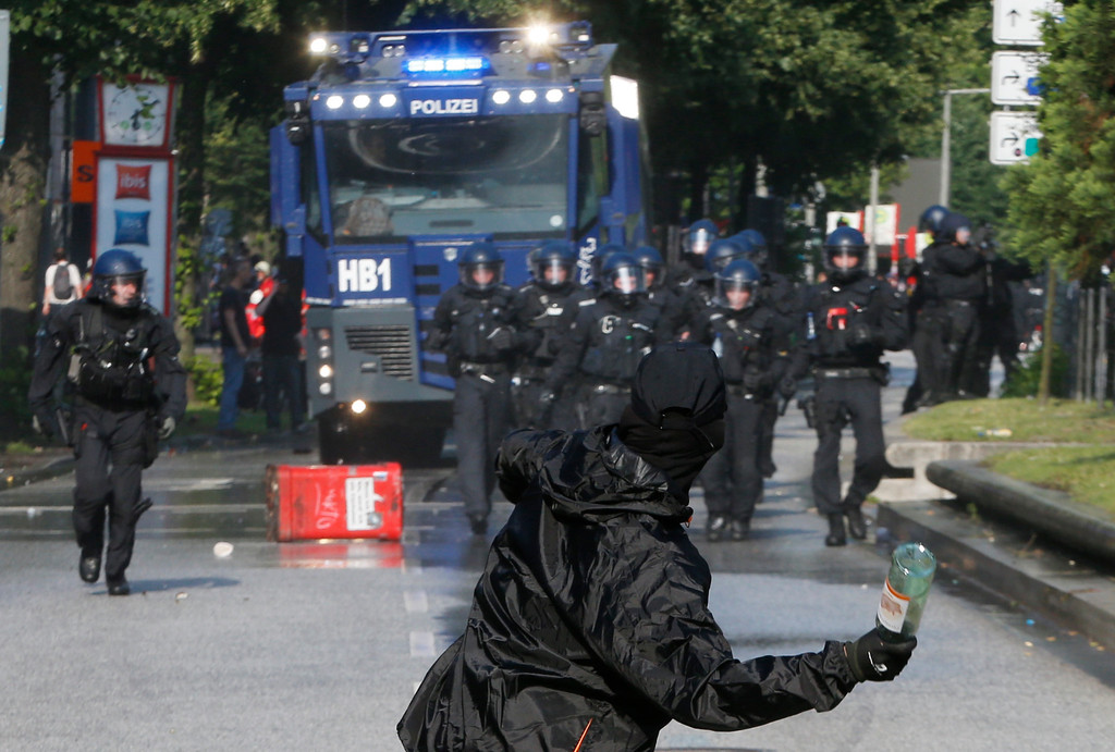 . A demonstrator throws a bottle towards police on the first day of the G-20 summit in Hamburg, northern Germany, Friday, July 7, 2017. The leaders of the group of 20 meet July 7 and 8. (AP Photo/Michael Probst)