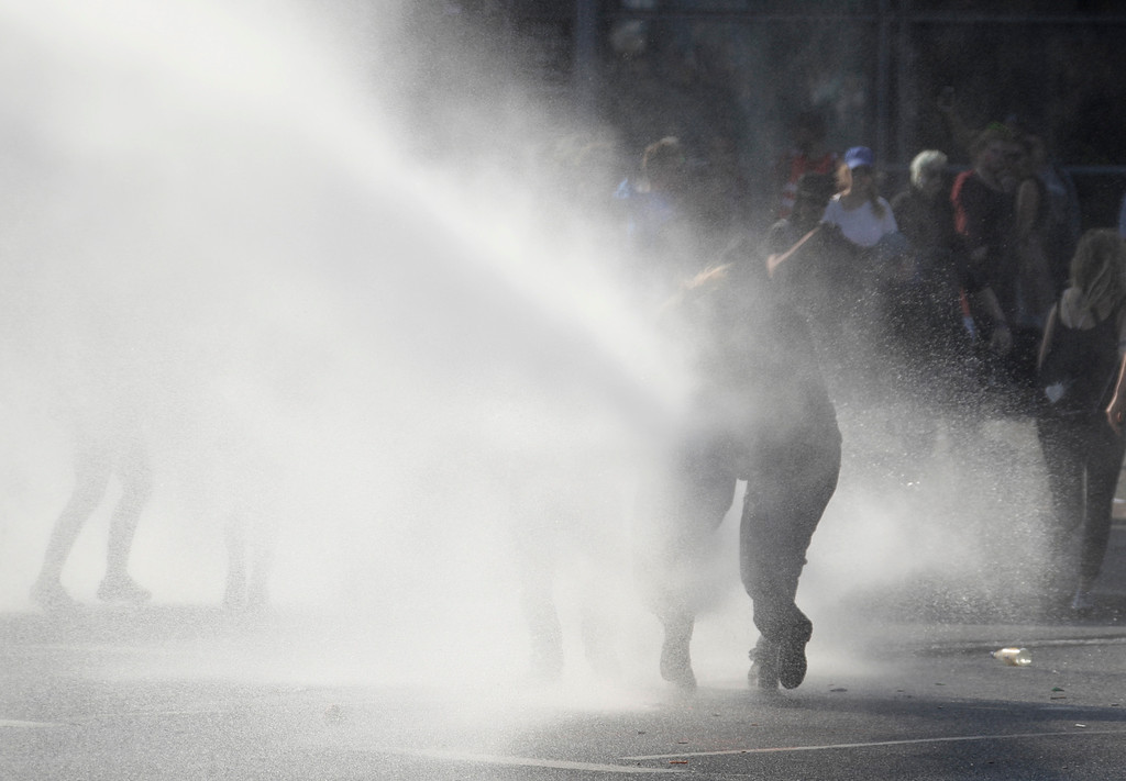 . Demonstrators are sprayed by a water cannon on the first day of the G-20 summit in Hamburg, northern Germany, Friday, July 7, 2017. The leaders of the group of 20 meet July 7 and 8. (AP Photo/Matthias Schrader)