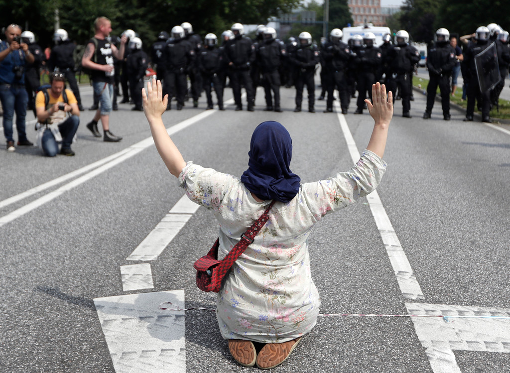 . A woman raises her arms as she kneels on a road in front of police officers on the first day of the G-20 summit in Hamburg, northern Germany, Friday, July 7, 2017. The leaders of the group of 20 meet July 7 and 8. (AP Photo/Matthias Schrader)