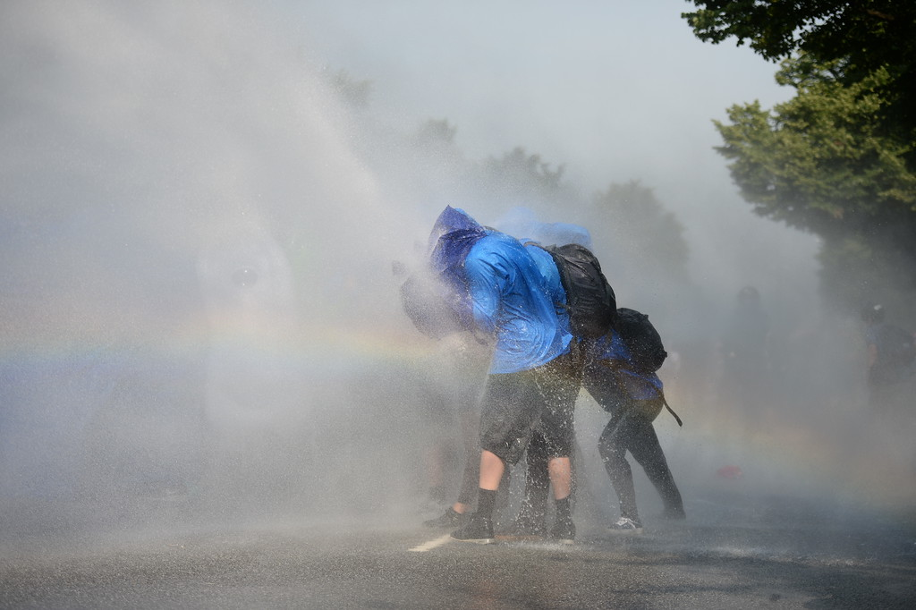 . Police uses water canons while demonstrators block a street during protests against the G-20 summit in Hamburg, Germany, Friday, July 7, 2017. The leaders of the group of 20 meet Friday and Saturday in Hamburg.  (Daniel Reinhardt/dpa via AP)