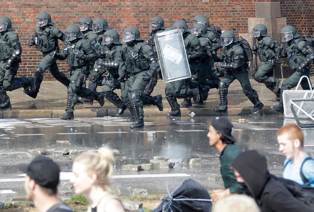 . Special police chase demonstrators who blocked a road on the first day of the G-20 summit in Hamburg, northern Germany, Friday, July 7, 2017. The leaders of the group of 20 meet July 7 and 8. (AP Photo/Matthias Schrader)