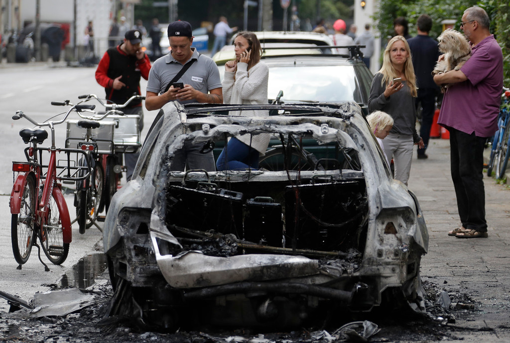 . People stand around a burnt car on the first day of the G-20 summit in Hamburg, northern Germany, Friday, July 7, 2017. The leaders of the group of 20 meet July 7 and 8. (AP Photo/Matthias Schrader)