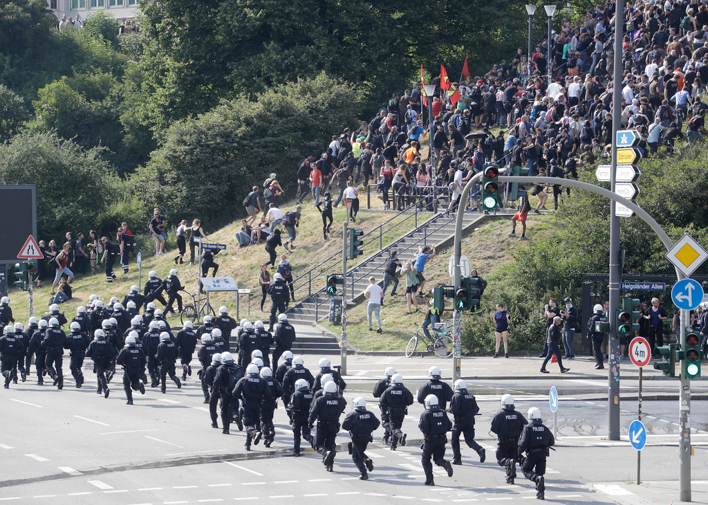 . Demonstrators who blocked a street flee from police on the first day of the G-20 summit in Hamburg, northern Germany, Friday, July 7, 2017. The leaders of the group of 20 meet July 7 and 8. (AP Photo/Matthias Schrader)