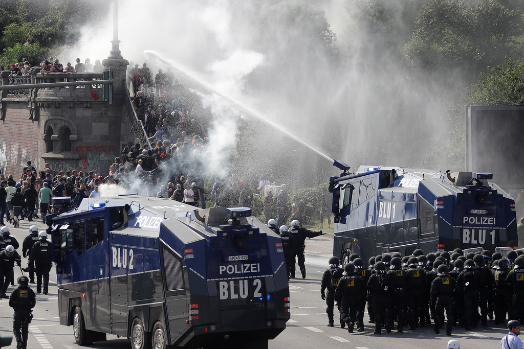 . Police use a water cannon to clear a road on the first day of the G-20 summit in Hamburg, northern Germany, Friday, July 7, 2017. The leaders of the group of 20 meet July 7 and 8. (AP Photo/Matthias Schrader)