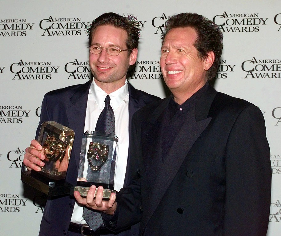 """. David Duchovney, left, poses with his award for Funniest Male Guest Appearance in a Television Series for \""""The Larry Sanders Show\"""" along with Garry Shandling who won for Funniest Male Performer in a Television Series, also for \""""The Larry Sanders Show,\"""" at the 13th Annual American Comedy Awards, Sunday, Feb. 7, 1999, in Los Angeles. The show will air on March 15. (AP Photo/Mark J. Terrill)"""