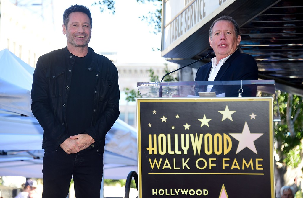 . File - Actor David Duchovny reacts as Garry Shandling speaks during Duchovny\'s Hollywood Walk of Fame Star ceremony on January 25, 2016 in Hollywood, California. (FREDERIC J. BROWN/AFP/Getty Images)