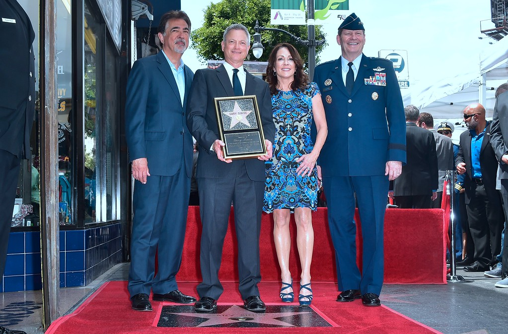 . Actor Gary Sinise (2nd L) olds a plaque while posing with Joe Mategna (L), Patricia Heaton (2nd R) and Air Force General Robin Rand (R) at his Walk of Fame Star ceremony in Hollywood, California on April 17, 2017, where Sinise was the recipient of the 2,606th star in the category of television. (FREDERIC J. BROWN/AFP/Getty Images)