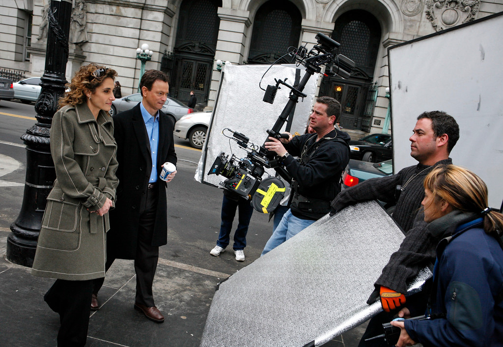 ". Actress Melina Kanakaredes, left, and actor Gary Sinise shoot a scene together during filming for an upcoming episode of CBS\'s ""CSI:NY\"" television drama near City Hall Thursday, March 22, 2007 in New York. (AP Photo/Jason DeCrow)"