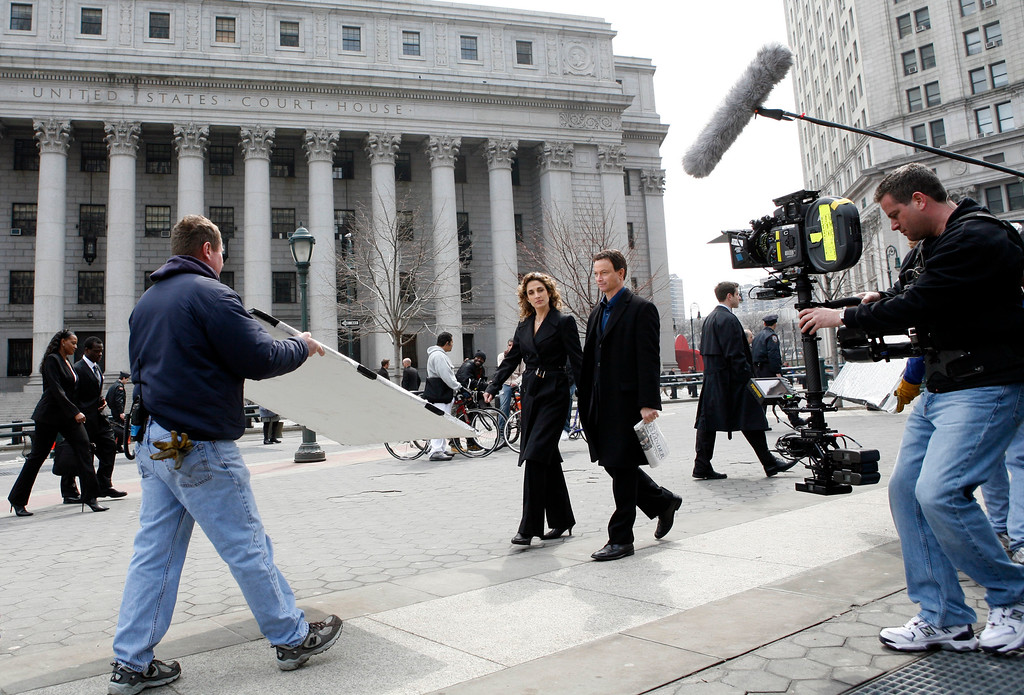""". Actress Melina Kanakaredes, left, and actor Gary Sinise shoot a scene together outside the federal courthouse during filming for an upcoming episode of CBS\'s \""""CSI:NY\"""" in Manhattan\'s Foley Square Thursday, March 22, 2007 in New York.   (AP Photo/Jason DeCrow)"""