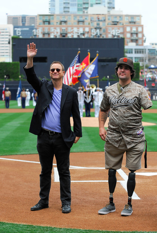 . SAN DIEGO, CA - APRIL 13:  Actor Gary Sinise (L) waves as he stands on the field with Marine Corps Sgt. Nick Kimmel as part of Military Opening Day before an inter-league baseball game between the Detroit Tigers and the San Diego Padres at Petco Park April 13, 2014 in San Diego, California.  (Photo by Denis Poroy/Getty Images)