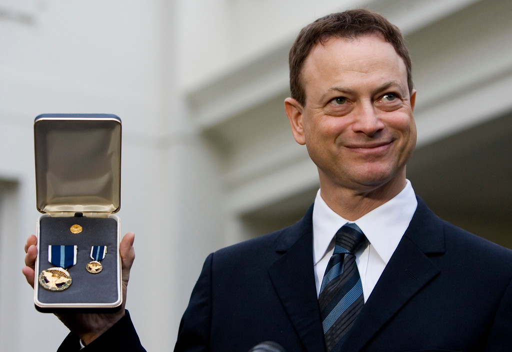 . Actor Gary Sinise, a recipient of the 2008 Presidential Citizens Medal, displays his medal while speaking with members of the press, Wednesday, Dec. 10, 2008, outside the White House in Washington. (AP Photo/Haraz N. Ghanbari)