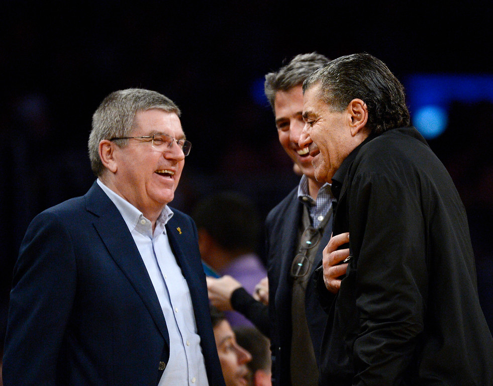 . LOS ANGELES, CA - JANUARY 31: Thomas Bach (L), president of the International Olympic Committee, greets sports agent Casey Wasserman (C) and film producer Haim Saban during the basketball game between the Los Angeles lakers and Charlotte Hornets at Staples Center January 31, 2016, in Los Angeles, California.  (Photo by Kevork Djansezian/Getty Images)