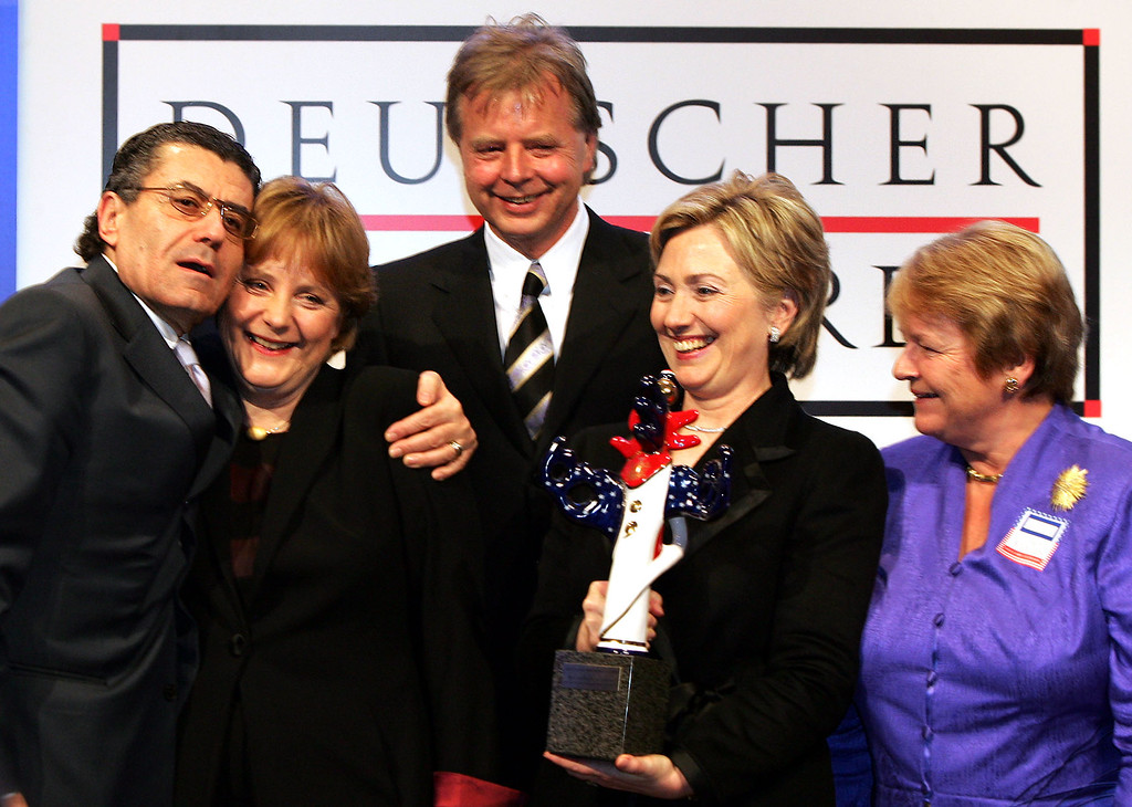 ". Hillary Clinton, D-N.Y., appears with Karlheinz Koegel, center, German Chancellor Angela Merkel, second from left, U.S. billionaire Haim Saban, left, and former Norwegian Prime Minister Gro Brundtland, holding the German Media Prize she was awarded in Baden-Baden, southern Germany, in this Feb. 13, 2005, file photo for her ""example in boosting the role of women in politics, business and media.\"" Clinton hopes to raise at least $75 million in 2007 for her presidential campaign, and her network includes many fundraisers from former President Clinton\'s campaigns, including Saban, left, the Hollywood studio investor and creator of the Mighty Morphin Power Rangers. (AP Photo/Winfried Rothermel, File)"