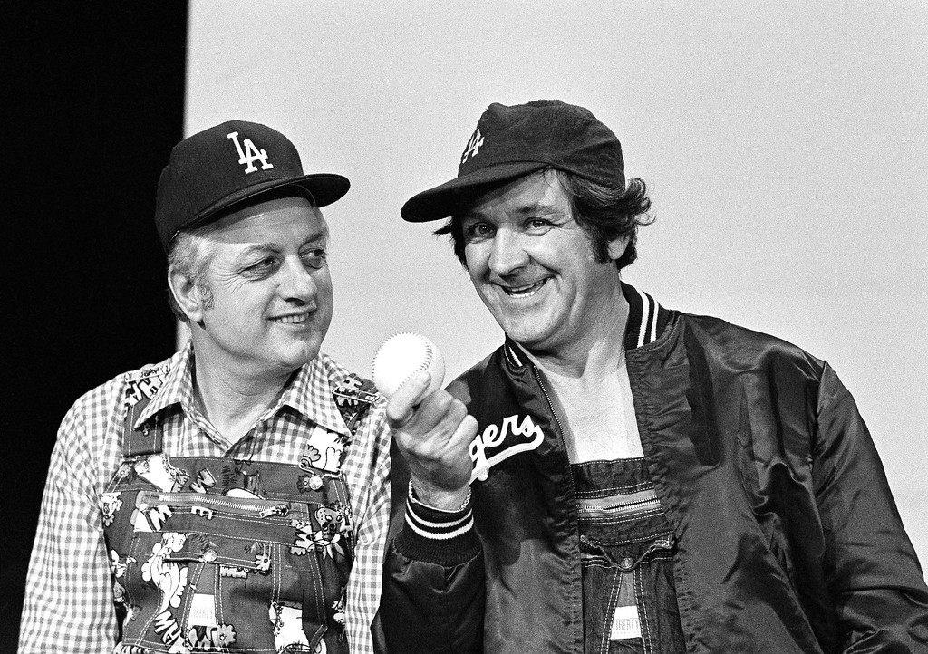 ". Tommy Lasorda (left) who managed the Los Angeles Dodgers into the World Series only to lose to the New York Yankees, takes a turn at slapstick humor as he makes a guest appearance on the TV show ""Hee Haw.\"" George Lindsey, a regular on the show that features dry, corny jokes, gives Lasorda some pointers on how to gag up a joke in Los Angeles on Oct. 16, 1977. (AP Photo/Nick Ut)"
