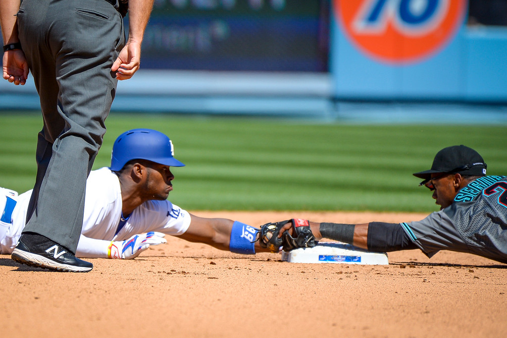 . Dodgers Yasiel Puig and Diamondacks Jean Segura face off at second base after Puig slide into second.  After a long review Puig was called safe on the play in the fifth inning.  Dodgers lost the home opener to the Diamondbacks 4-2.   (Photo by David Crane Southern California News Group)