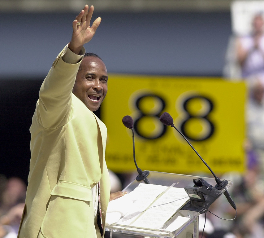 . Pro Football Hall of Fame enshrinee Lynn Swann waves to the crowd as fans hold a banner bearing his jersey number in the background during the enshrinement ceremony on 04 August 2001 at the Pro Football Hall of Fame in Canton, OH. Swann was named USC�s athletic director on Wednesday, April 13, 2016.   (DAVID MAXWELL/AFP/Getty Images)
